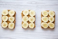 Vegan toasts with peanut butter and banana on a white wooden background,. From above royalty free stock image