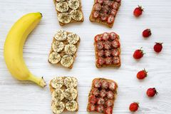 Vegan toasts with peanut butter, fruits and chia seeds on a white wooden table, top view. Some ingredients. Healthy breakfast Royalty Free Stock Photos