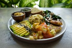 Vegan tofu with avocado, bread, vegetables and source close-up on a plate. Stock Image