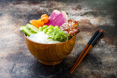 Vegan tofu poke bowls with seaweed, watermelon radish, cucumber, edamame beans and rice noodles. Copy space. Background stock photo