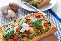 Vegan tofu quiche with spinach and mushrooms and tomato stock photo