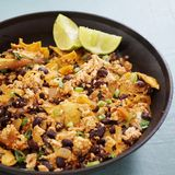 Vegan tofu scramble chilaquiles. With beans, scallions and lime Stock Images