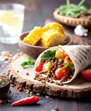 Vegan tortilla wrap, roll with grilled vegetabes, lentil, corn cob. Vegan tortilla wrap, roll with grilled vegetabes and lentil and boiled corn cob on a wooden royalty free stock photography