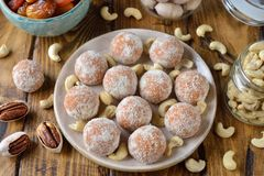Vegan truffles from dried fruits and cashews. On a brown background royalty free stock photography