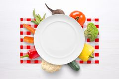 Vegan vegetables concept with empty plate and vegetables on red white table cloth. Flat lay Stock Image