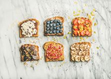 Vegan whole grain toasts with fruit, seeds, nuts, peanut butter Stock Photos