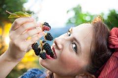 Vegan woman. Eating wild fruits in nature stock photo