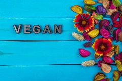 Vegan word on blue wood with flower royalty free stock photography