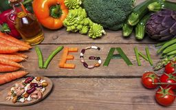 Vegan word on wood background and vegetable - food Royalty Free Stock Image