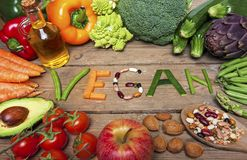 Vegan word on wood background and vegetable - food Stock Images