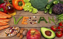 Vegan word on wood background and vegetable - food Royalty Free Stock Photos