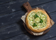 Vegan zucchini pizza on a rustic cutting board on dark wooden background. Royalty Free Stock Photos