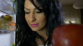 Veganistvrouw het openen koelkast ruikende vruchten en het nemen van een appel voor brunch stock videobeelden