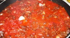Vegano che cucina giaca bolognese con i pomodori e le cipolle di inverno fotografia stock