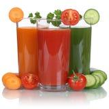 Vegano sano que come el jugo vegetal de las zanahorias, tomates y Foto de archivo libre de regalías