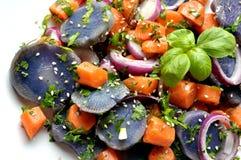 Vegansalat mit violetter Kartoffel, Karotten und Zwiebel Lizenzfreies Stockfoto