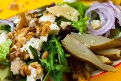 Vege沙拉用梨、核桃、乳酪和绿色叶子 免版税库存照片