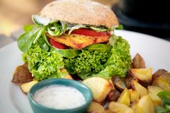 Vegean burger with lettuce, tomato, and potato stock photography