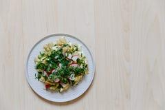 Vegetable салат с редиской, свежими огурцами, картошками и зелеными луками на белом взгляд сверху плиты Стоковые Изображения