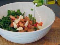 Vegetable салат салата Оливковое масло лить в шар салата стоковые изображения