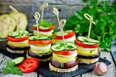 Vegetable towers of eggplant, pepper, tomato, cucumber on toasted bread with skewers. Vegetable appetizer towers of eggplant, pepper, tomato, cucumber on toasted stock images