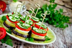 Vegetable appetizer of eggplant, pepper, tomato, cucumber on toasted bread with skewers. Vegetable appetizer towers of eggplant, pepper, tomato, cucumber on stock photos