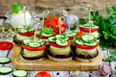 Vegetable towers of eggplant, pepper, tomato, cucumber on toasted bread with skewers. Vegetable appetizer towers of eggplant, pepper, tomato, cucumber on toasted stock photos