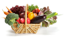 Vegetable Basket. Basket of Various Vegetables with Broccoli, radishes, lettuce, onions, leeks, beets, carrots, red tomatoes, yellow tomatoes, parsley isolated Stock Photo