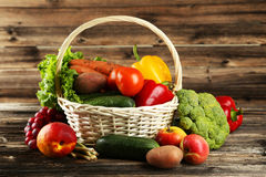 Vegetable in basket on brown wooden background. Royalty Free Stock Photos