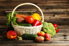Vegetable in basket on brown wooden background. Royalty Free Stock Images