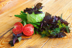Vegetable bouquet on a wooden table. Still life with tomatoes, basil, onion and cabbage on a wooden table Stock Photo