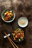 Vegetable in bowl stir fry on wok on concrete dark background royalty free stock photos