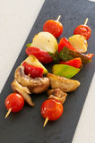 Vegetable brochettes. On a black slate tray Stock Photos
