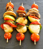 Vegetable brochettes on a black slate tray. Three Vegetable brochettes on a black slate tray Royalty Free Stock Image