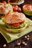 Vegetable burger with chickpeas - spinach fritter, lettuce and tomato Stock Image