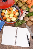 Vegetable casserole dish with cookbook, copy space, vertical Stock Photos