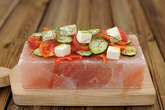 Vegetable and cheese salad served on a block on himalayan pink s. Alt Royalty Free Stock Photos