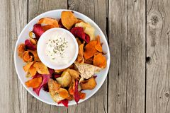 Vegetable chips with dip overhead view on rustic wood Stock Images