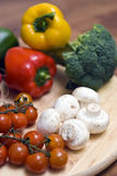 Vegetable composition. Some vegetables arranged on a wooden chopping board. Tomatoes, mushroom, peppers, broccoli royalty free stock images