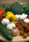 Vegetable composition. Some vegetables arranged on a round wooden chopping board. Tomatoes, mushroom, peppers, broccoli Stock Photos