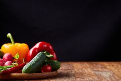 Composition of vegetables on flat plate on wooden table, close-up, selective focus. Vegetable composition of cucumber, tomatoes, and red and yellow bell pepper stock image
