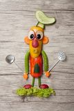 Vegetable cook with spoons on wooden background. Cook made of pepper, cucumber, carrot, radish, pea, and olive. Holds metal kitchen spoons. Wooden background Stock Images