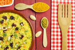 Vegetable couscous in a clay pot. With some ingredients, spices and a wooden fork Royalty Free Stock Image