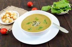Vegetable cream суп с шпинатом и картошками в белом шаре с гренками чеснока на темной деревянной предпосылке Стоковая Фотография RF