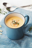Vegetable cream soup from carrot and potato decorated almonds flakes in blue bowl on rustic background. Vegetable cream soup from carrot and potato decorated Stock Image