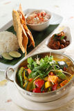 Vegetable Curry. A bowl of vegetable curry with rice and other side dishes Stock Photo