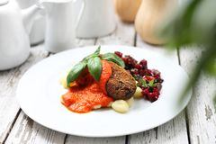 Vegetable cutlets served with tomato sauce on dumplings on gnocchi, roasted beetroot salad royalty free stock photography