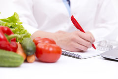 Vegetable diet nutrition or medicaments concept. Doctors hands writing diet plan, ripe vegetable composition, laptop and measuring Royalty Free Stock Image