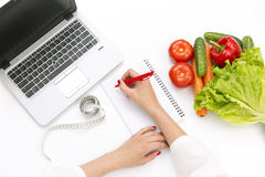 Vegetable diet nutrition or medicaments concept. Doctors hands writing diet plan, ripe vegetable composition, laptop and measuring. Tape on white background royalty free stock photography