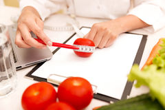Vegetable diet nutrition or medicaments concept. Female nutrition doctor with vegetables and measuring tape on table.  stock images